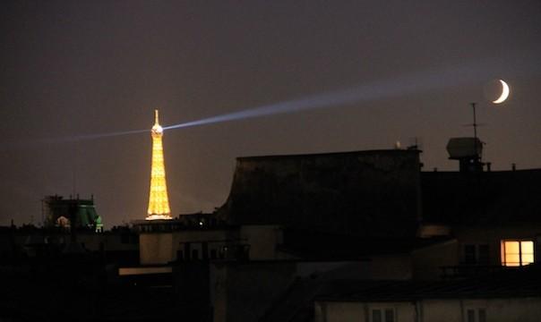 Un phare de la Tour Eiffel braqué sur le croissant de lune.
