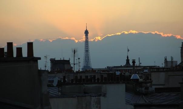 La Tour Eiffel éclairée par un nuage de lumière.
